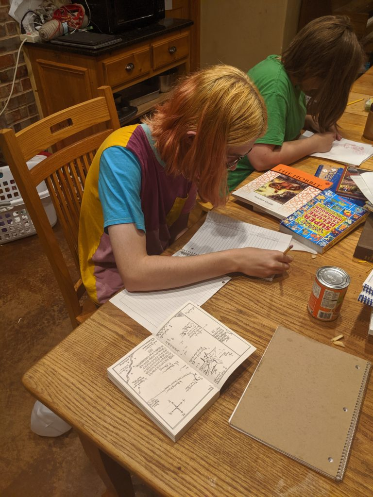 Blond teenager copying a map inscribed with runes from The Hobbit, another teen writing, table covered with books and papers